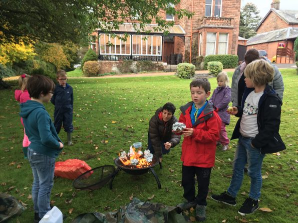 Children round campfire cooking apples